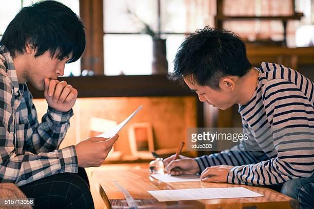 2 つの若い大人男性ペーパーズ記入する