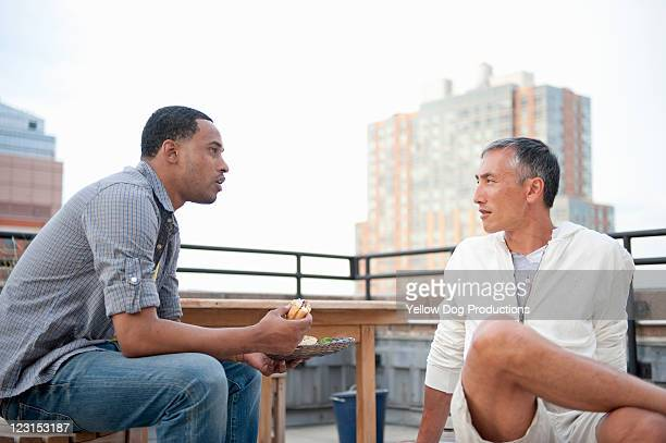 Two Young Adult Men Talking at Rooftop Party