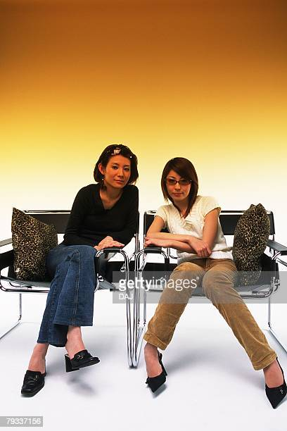 Two Young Adult Women Sitting on Chairs With a Fading Brown Backround, Front View, Looking at Camera