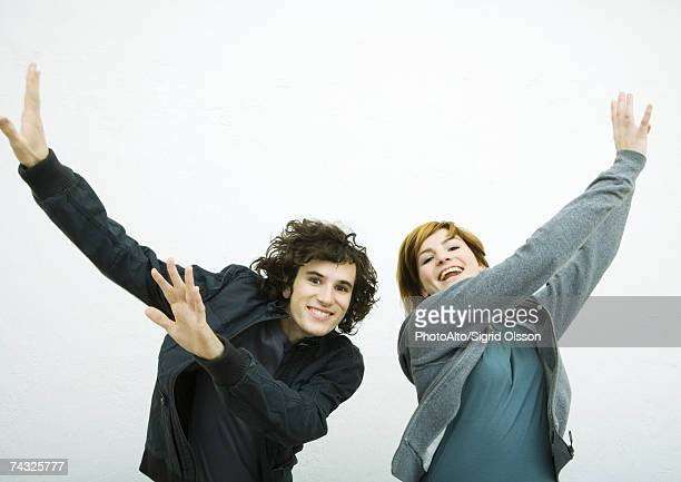 Two young adults, dancing, white background