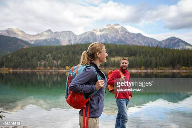 Two young adults hiking by the lake