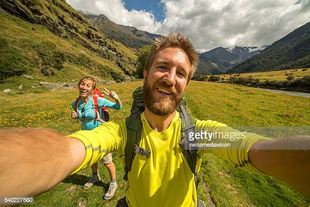 Two young adults hiking take self portrait in nature