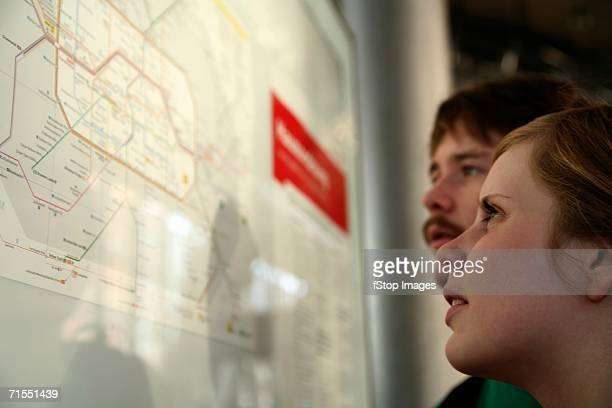 Two young adults looking at a subway map, Berlin, Germany