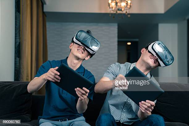 Two young adults playing games on virtual reality headsets