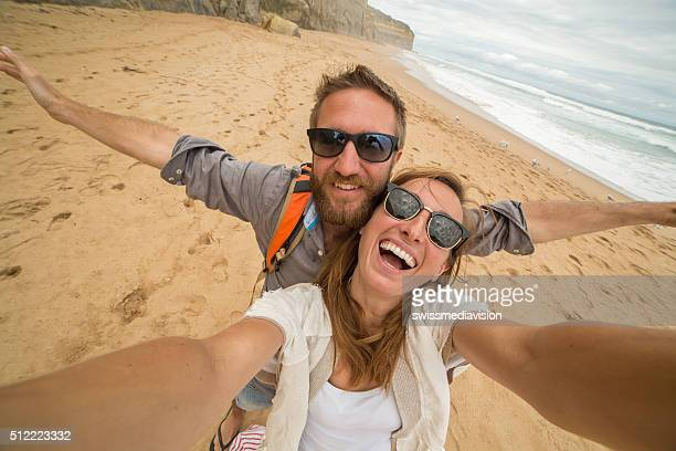 Two young adults take a selfie portrait on the beach