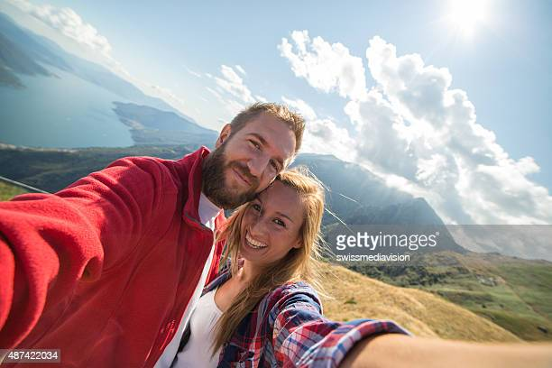 Two young adults taking selfie at mountain top