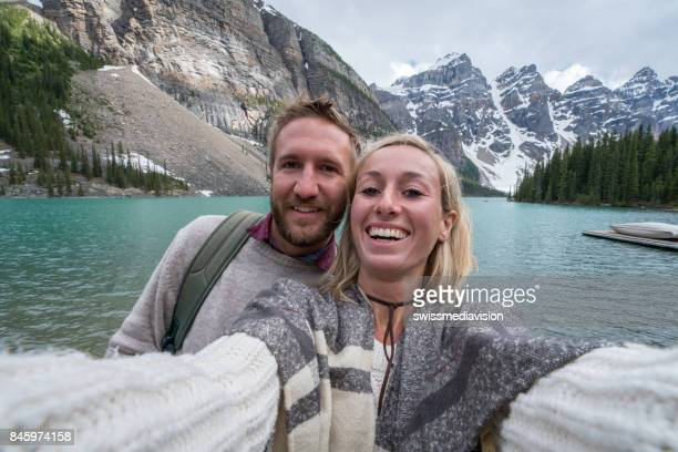 Two young adults taking selfie portrait at mountain lake