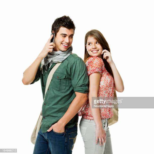 Two Young Adults Talking on Cellphones - Isolated