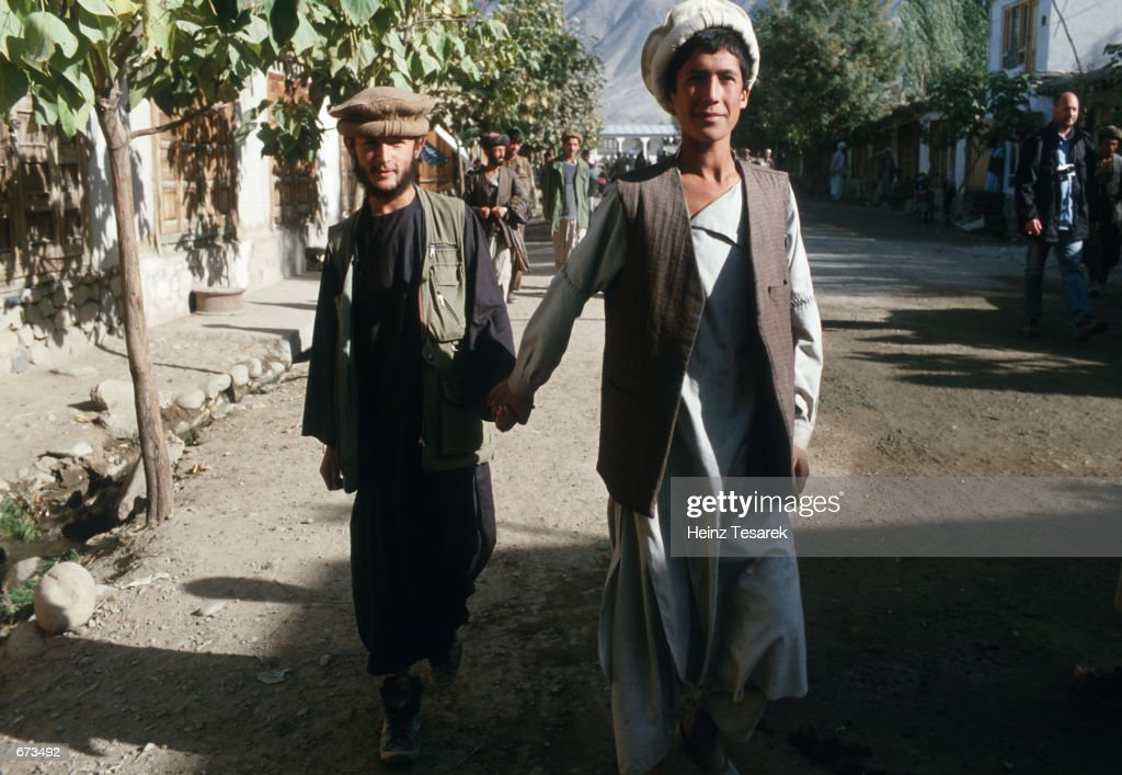 Two young Afghan boys walking hand in hand October 9 2001 in the streets of Jorm northern Afghanistan Holding hands in common among men in the region