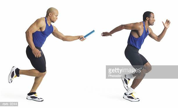 two young african american male track runners and teammates pass the baton during a race