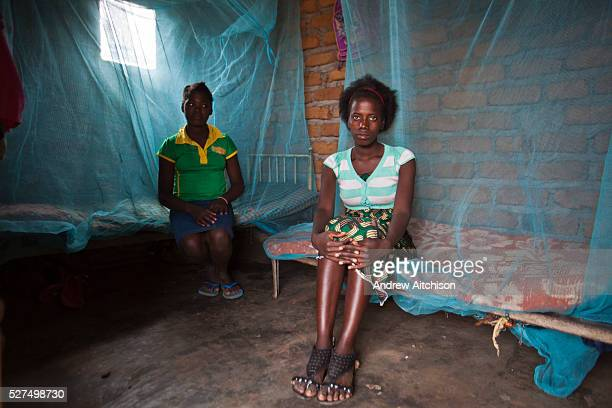 Two young African girls sit on their beds in their basic bedrooms in the children's home run by the Evangelical Church of Mozambique in Chimoio...