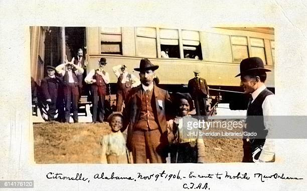 Two young AfricanAmerican children posing with a railroad conductor during a stop in Citronelle Alabama a train car visible in the background...