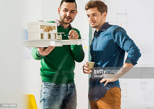 Two young architects in office discussing architectural model