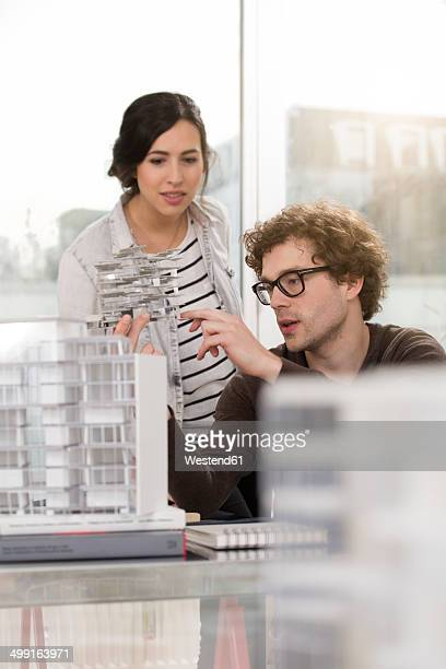 Two young architects with architectural model in office