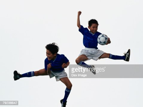 Two young Asian boys playing football in mid-air : Stock Photo