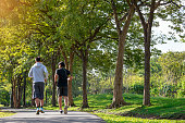 Two young Asian men running in the park, fitness sport and lifestyle concept