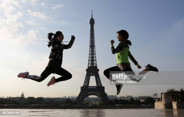 TOPSHOT Two young Asian women jump simultaneously for a souvenir picture near the Eiffel Tower at the Palais de Chaillot on early July 26 2017 in...