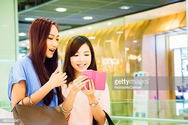 Duas jovens mulheres asiáticas redes sociais em shopping mall