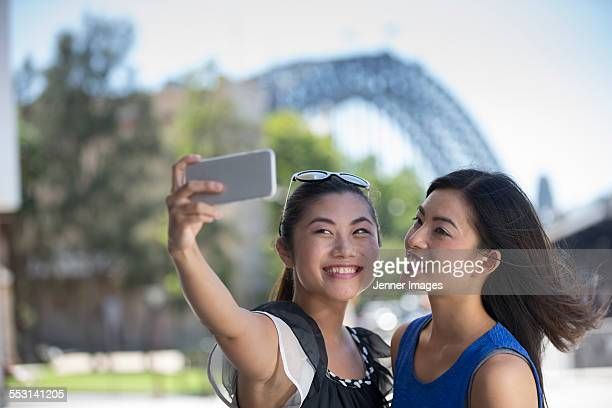 Two young asian women taking a selfie.
