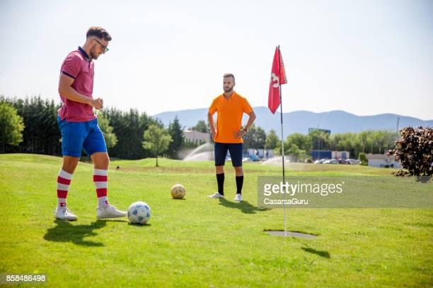 Two Young Athlete Playing FootGolf