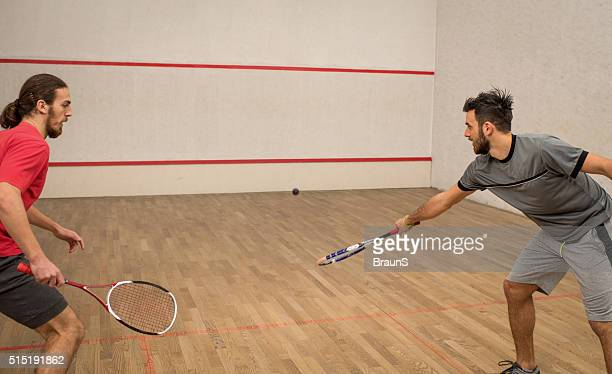 Two young athletic men playing squash on a court.