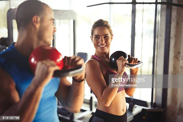 Two young athletic people doing kettlebell exercises at gym.
