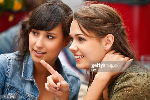 Two young  attractive women in street cafe, one pointing