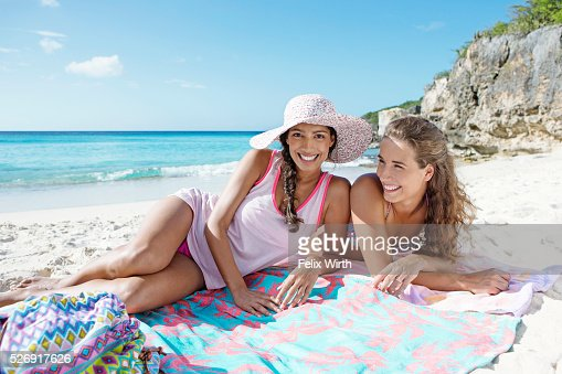 Two young attractive women resting on beach : Foto stock