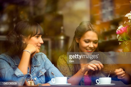 Two Young Beautiful Women Sitting in a Cafe : Stock Photo