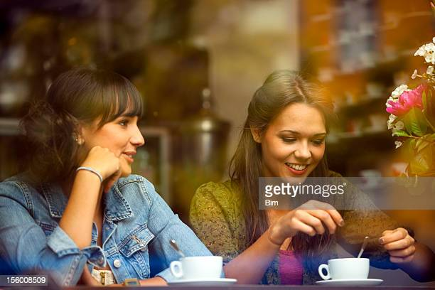 Two Young Beautiful Women Sitting in a Cafe