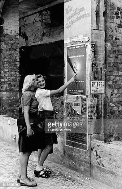 Two young Berlin women study a poster inviting Berliners to the Tattoo Germany 1947