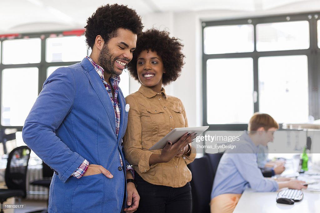 Two young black entrepreneurs in a new startup business : Stock Photo
