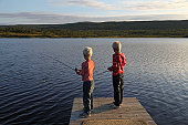 Two young blonde boys fishing in lake in mountain