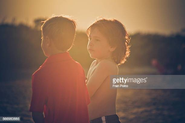 Two young boys at the beach at sunset.