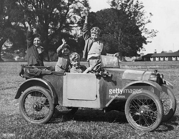 Two young boys drive their friends round a field in an Austin Seven car from their father's garage in Titchmarsh Kettering