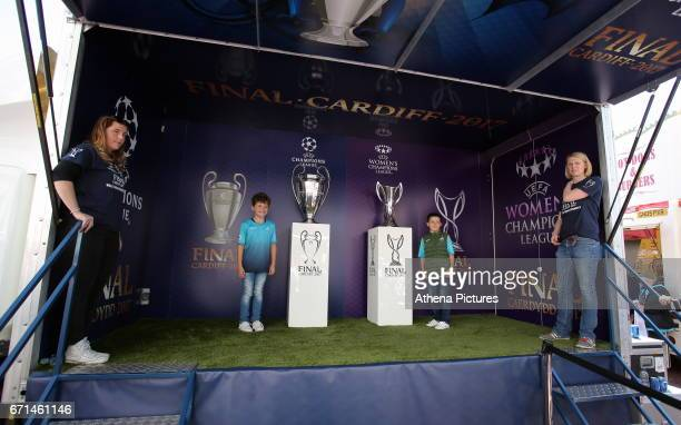 Two young boys have their picture taken by the Champions League and Women's Champions League trophies on display outside the stadium prior to the...
