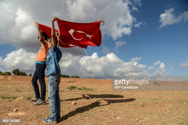 Two young boys hold up Turkish national flags during a demonstration in support of the Turkish army's Idlib operation near the TurkeySyria border...