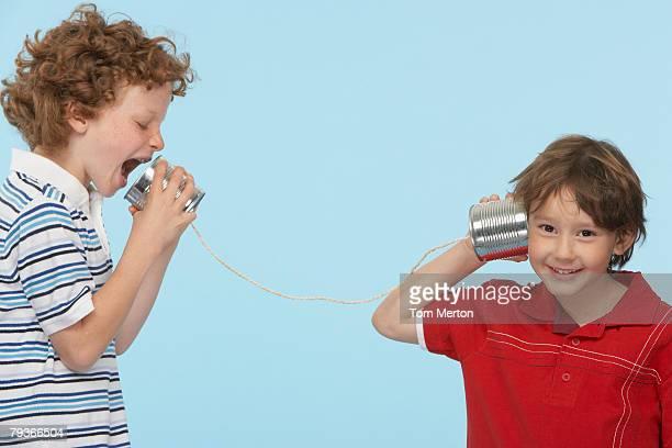 Zwei Jungen im Freien spielen mit Dosentelefon