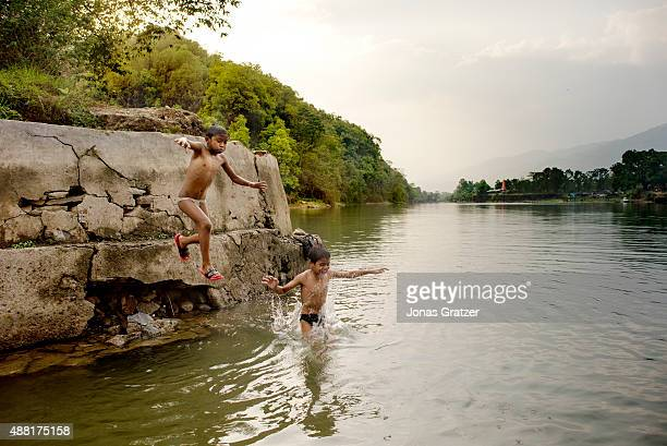 Two young boys jump from a small ledge on the side of the lake into the water Phewa Lake is a freshwater lake in Nepal located in the south of the...