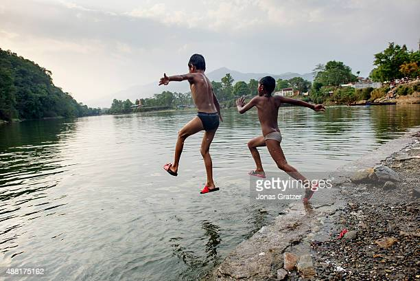 Two young boys jump off a ledge on the lakeside into the water Phewa Lake is a freshwater lake in Nepal located in the south of the Pokhara Valley...