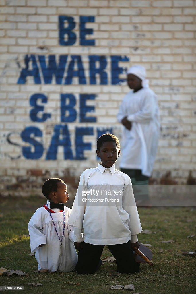 Two young boys look on as members of the Church of Nazareth take part in a service at Rockville School, in Soweto on June 15, 2013 in Johannesburg, South Africa. The Baptist church, which is a mixture of Zulu tradition and Christianity, continued their daily life as the former South African President and leader of the anti-apartheid movement who is spending a seventh night in hospital. It has been reported that he is responding better to treatment for a recurring lung infection.