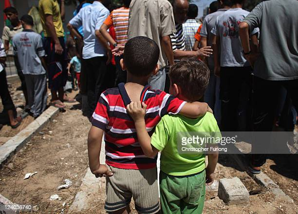 Two young boys look on as mourners attend the funeral of Palestinian Saad alMajdalali who was shot by border guards after venturing too close to the...