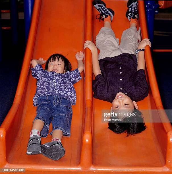 Two young boys (6-7) (8-9) lying on twin slippery slide, one upside down