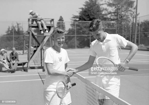Two young boys one substantially taller than than the other shake hands over the net of a tennis court before beginning a match with scorekeeper...