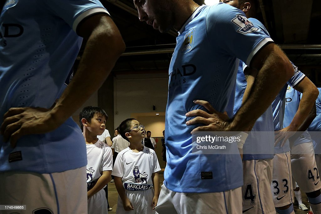 Two young boys participating in the opening ceremony look up at players from Manchester City as they wait in the tunnel during the Barclays Asia...