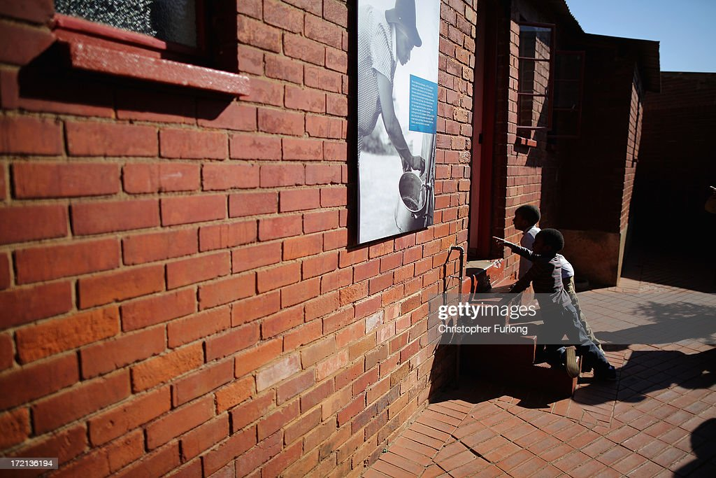 Two young boys peers through the back door of the 'Mandela House' museum at 8115 in Vilakazi Street in the Orlando West section of Soweto Township on July 2, 2013 in Soweto, Johannesburg, South Africa. 8115 is the location of the first house owned by former South African President Nelson Mandela where he lived for 44 years from 1946 to 1990. The 'Mandela House', now a museum is managed by the Soweto Heritage Trust which has seen an increase in vistors both local and international since Mandela was hospitalized with a lung infection on June 8, 2013 and still remains in a critcal condition.