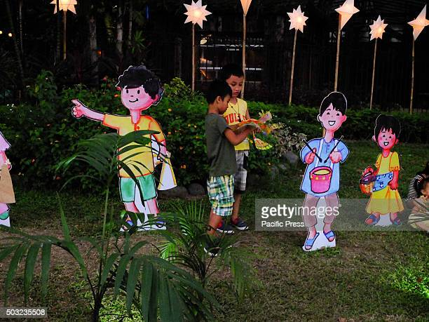 Two young boys playing alongside caricatures of children standees doing a caroling activity