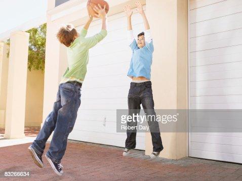 Two young boys playing basketball : Stock Photo