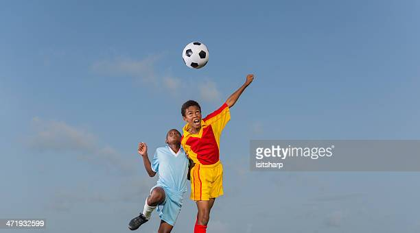 Two Young Boys Playing Football