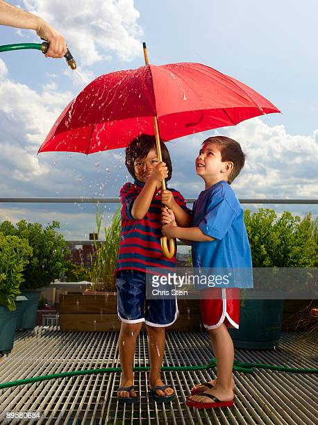 Two Young Boys playing with an umbrella